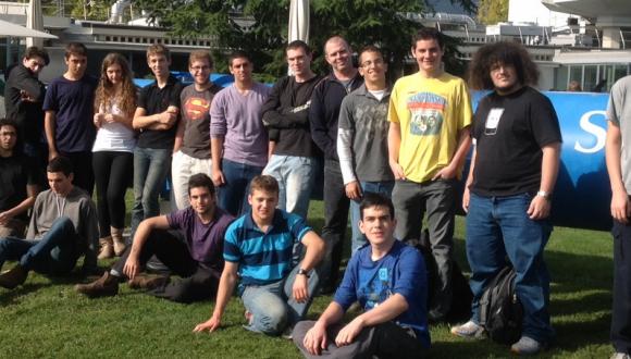 כל הקבוצה מחוץ לקפיטריה של CERN, כשמאחוריהם דגם הצינור שבו מאיצים הפרוטונים מתחת לאדמה